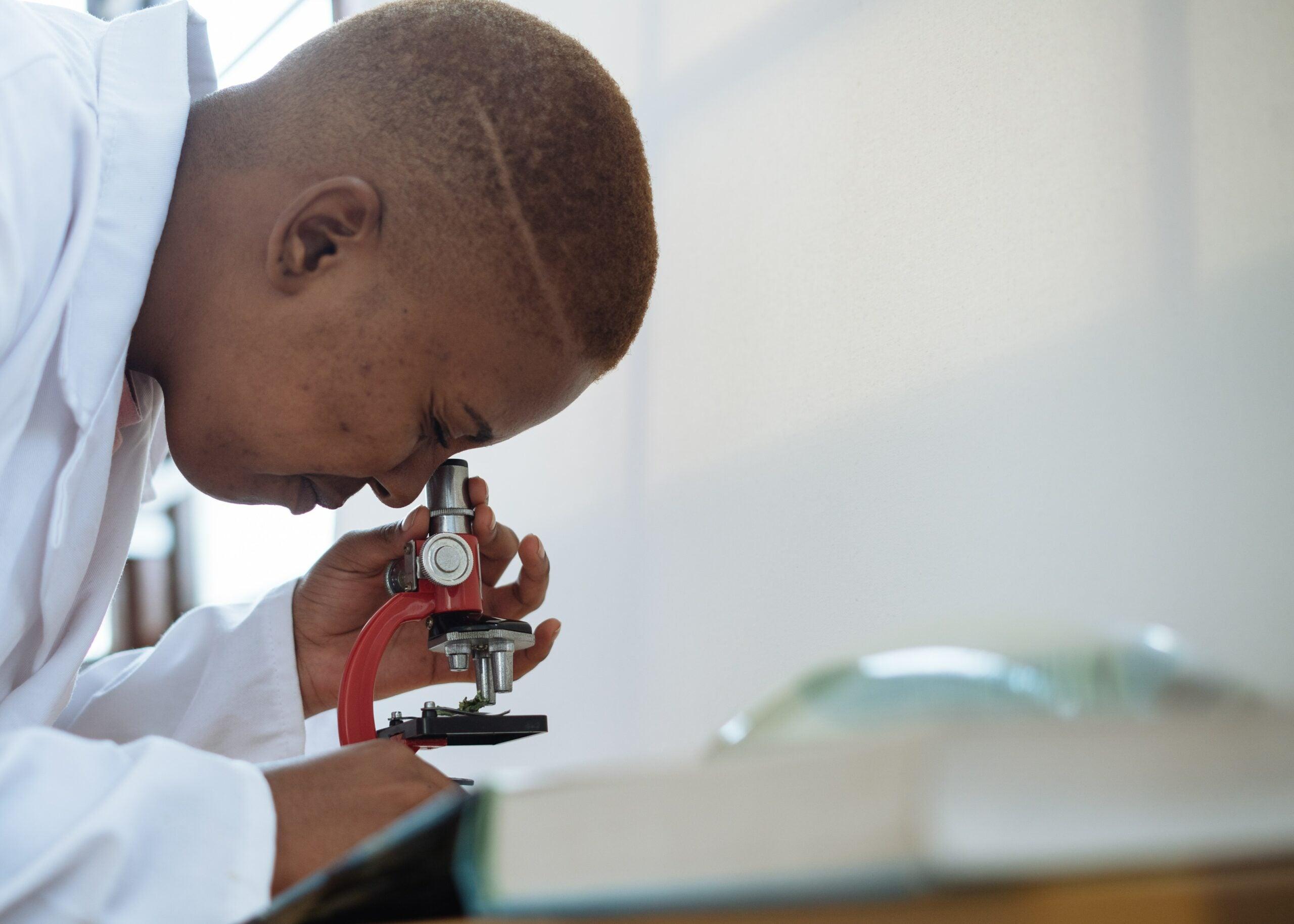 Laboratory scientist using microscope.
