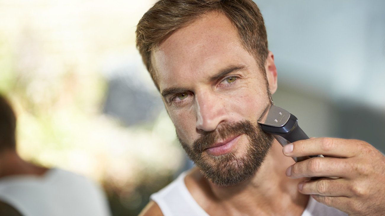 Man with a beard using an electric shaver.
