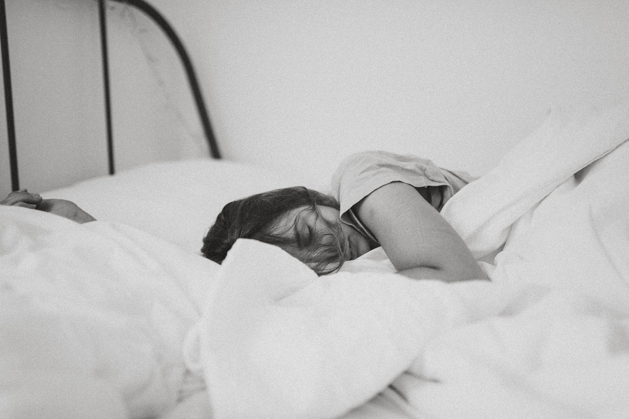 A woman sleeping in bed under a blanket and the best bed sheets.