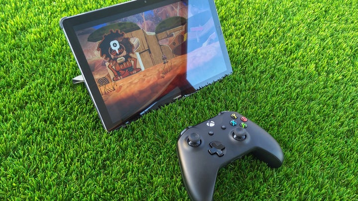 Samsung tablet on green grass with an xbox controller next to it