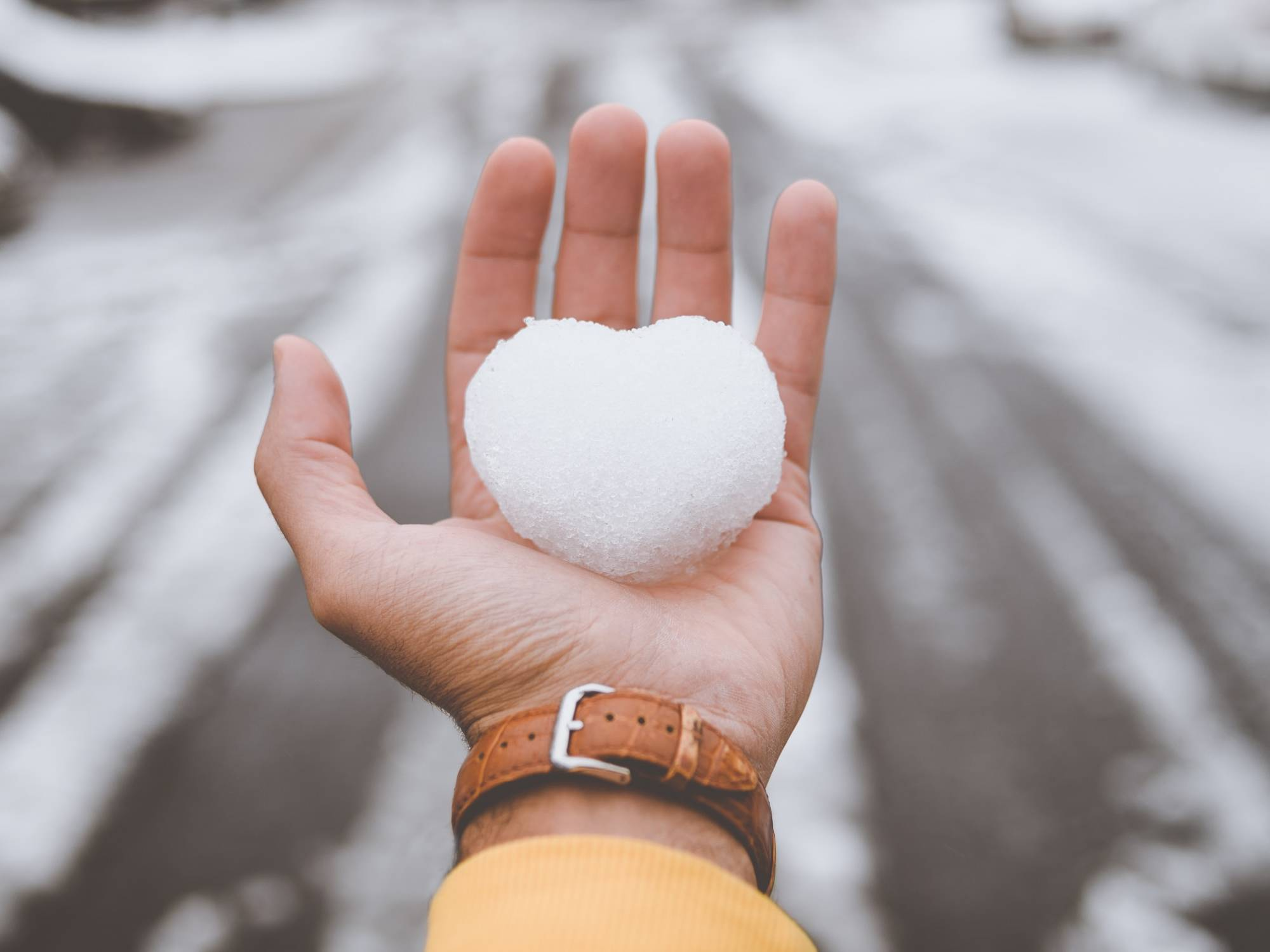 Bare hand holding heart-shaped snow ball.