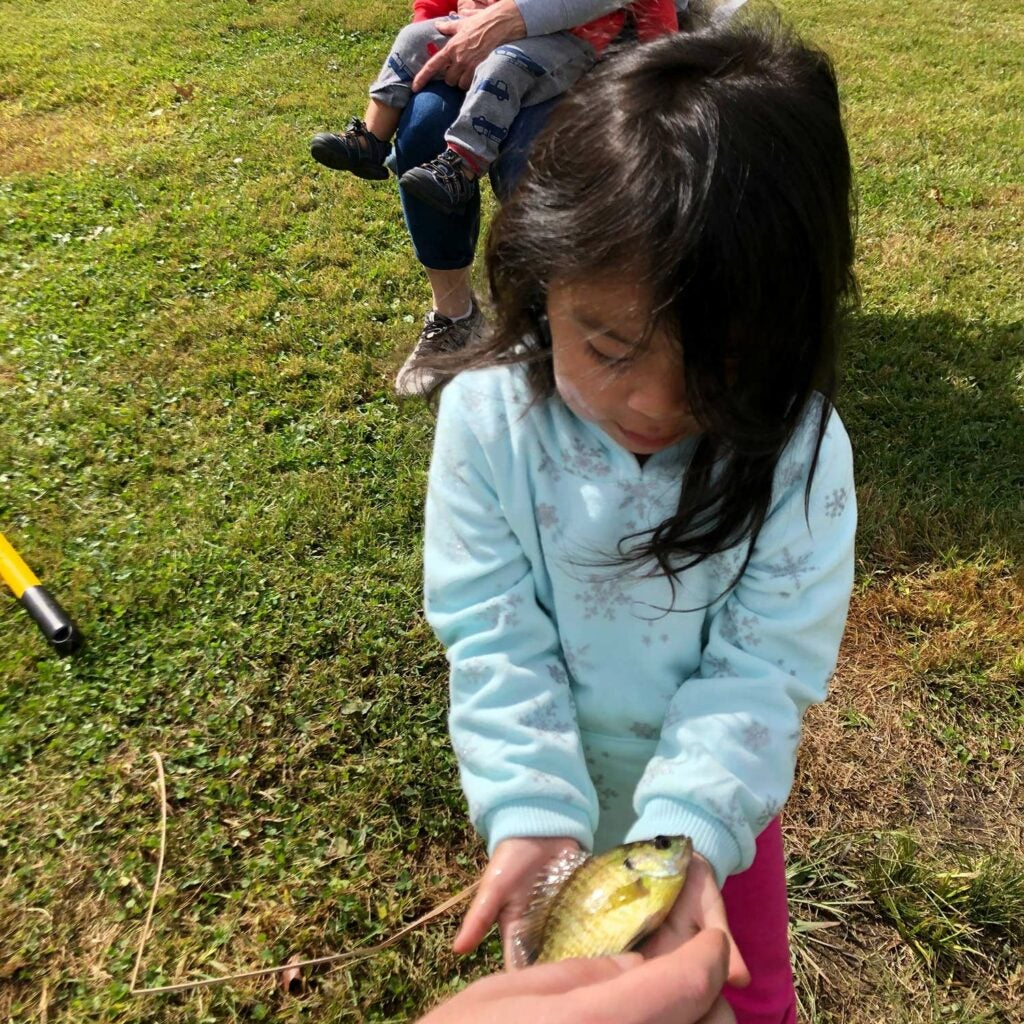 A young girl holds a small fish in her hands.