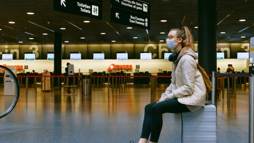 woman sitting on a suitcase in an airport wearing a face mask