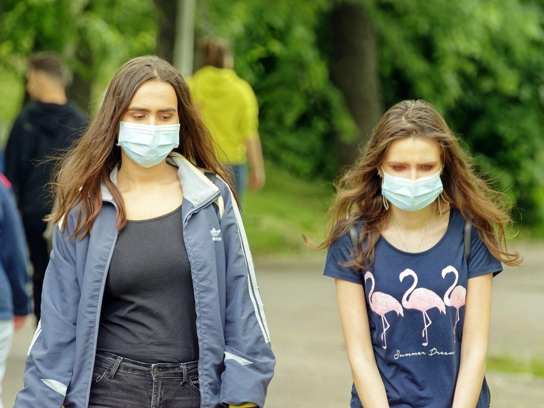 two women wearing masks outside