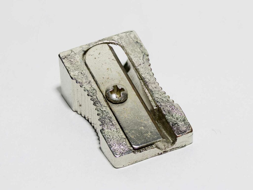 A metal pencil sharpener on a white background.