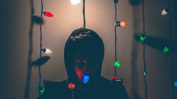 a person sitting under a light in a dark room, surrounded by holiday Christmas lights