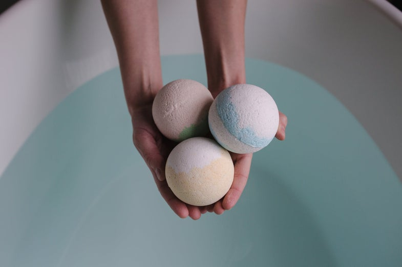 A woman holds three homemade bath bombs in her hand over a bath tub full of water.