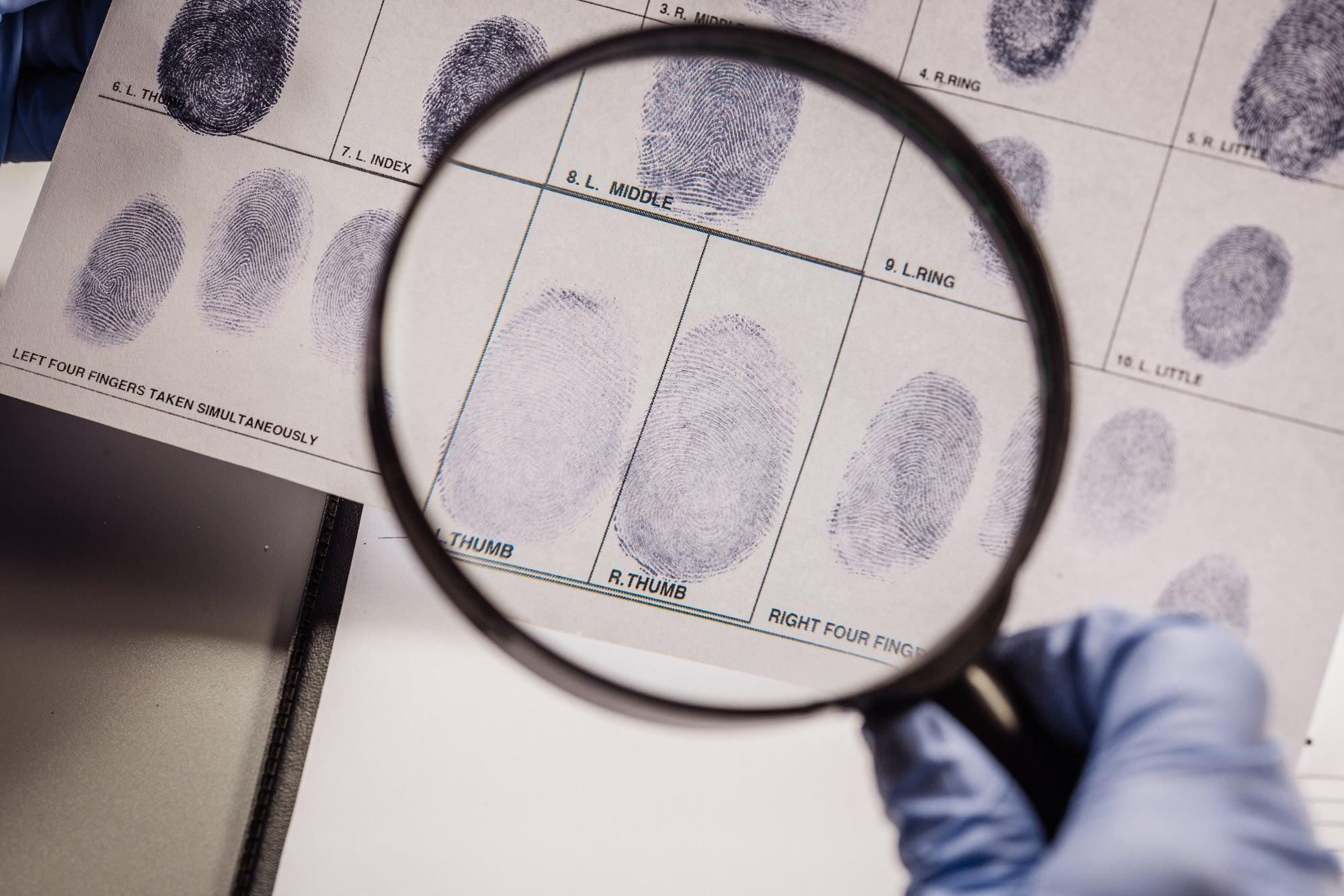 A gloved hand holding a magnifying glass and looking at fingerprints