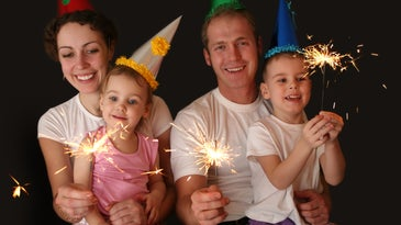 Parents and two kids on New Year's in party hats and sparklers