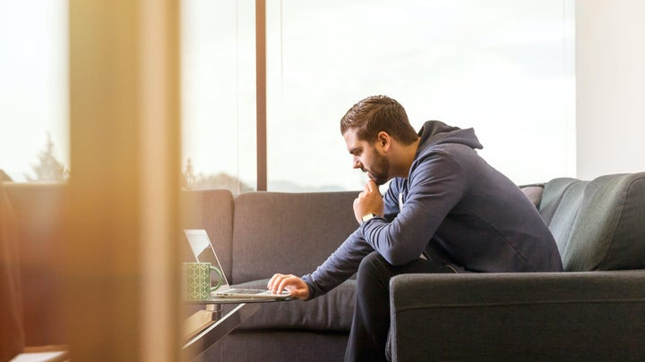 A man sitting on a couch while using a laptop on a table and holding his chin thoughtfully.