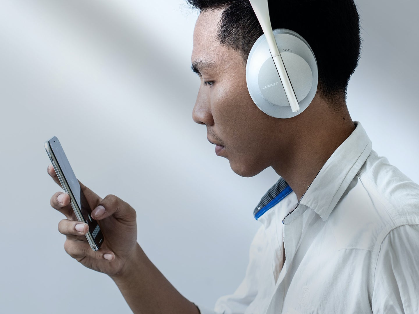 Person with headphones playing audio on smartphone