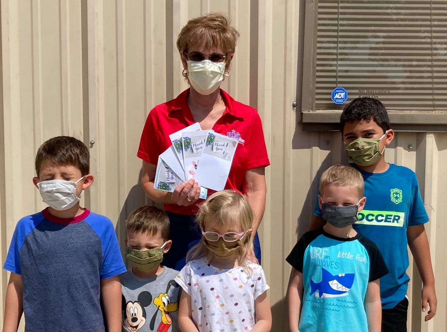 A nurse practitioner and kids wearing masks in front of a rural Texas COVID-19 clinic