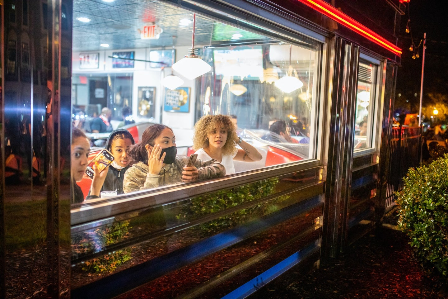 People wearing masks looking out the window of a diner during the COVID-19 pandemic