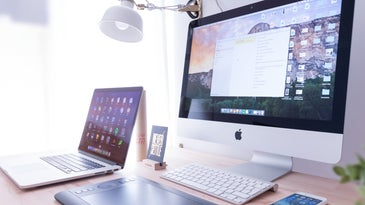 An Apple macOS laptop, desktop computer, tablet, and iOS iPhone on a wooden desk.