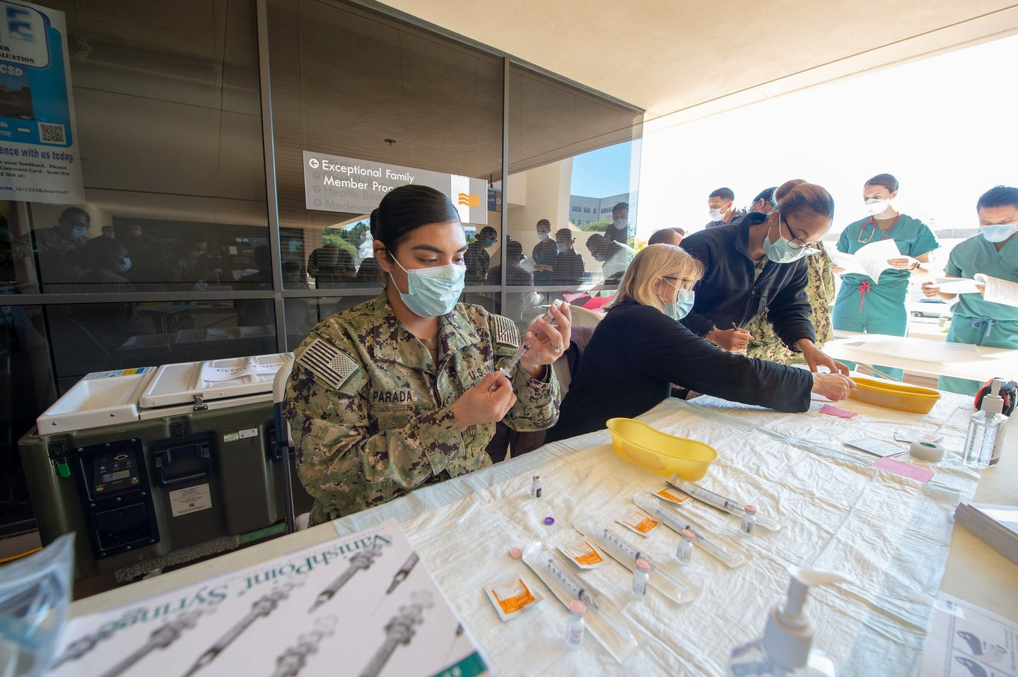 A US sailor at the Naval Medical Center in San Diego, California, prepares Pfizer COVID-19 vaccines for rollout
