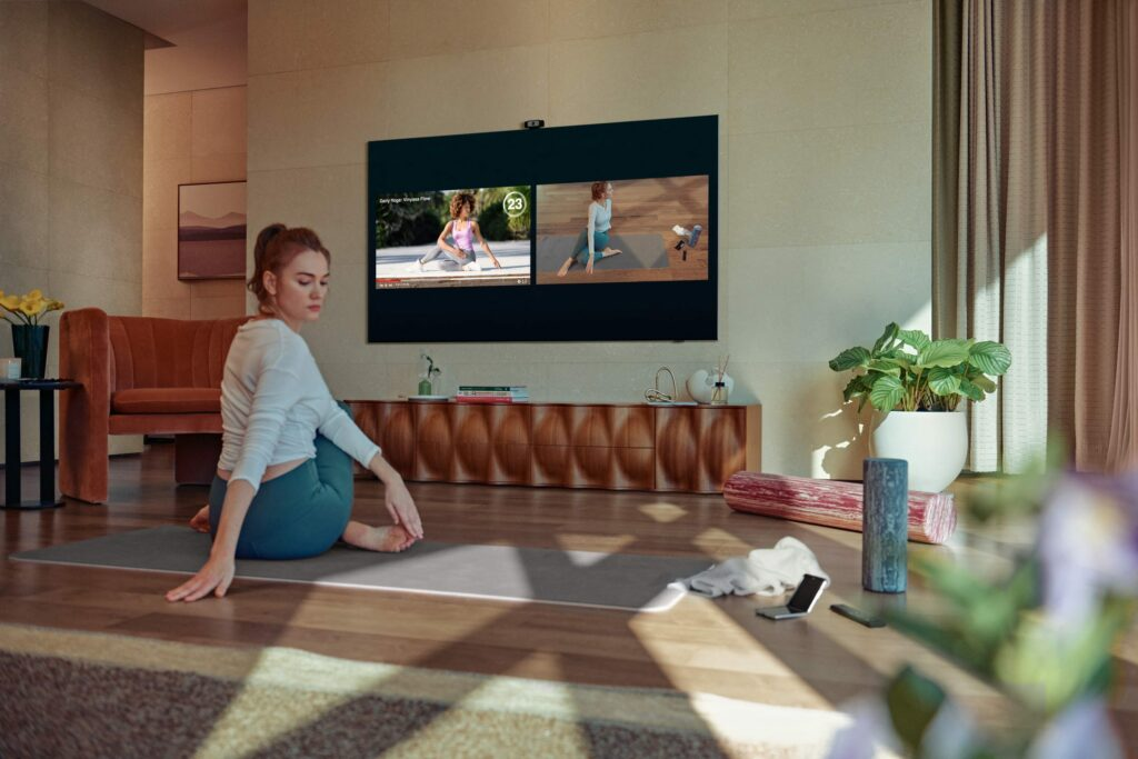 A woman doing yoga in front of a samsung TV.