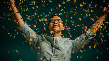 A person in glasses and a buttoned shirt tossing a handful of colorful confetti in the air