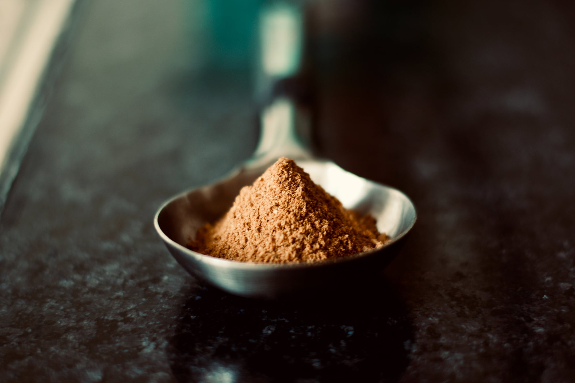 brown protein powder in a silver spoon