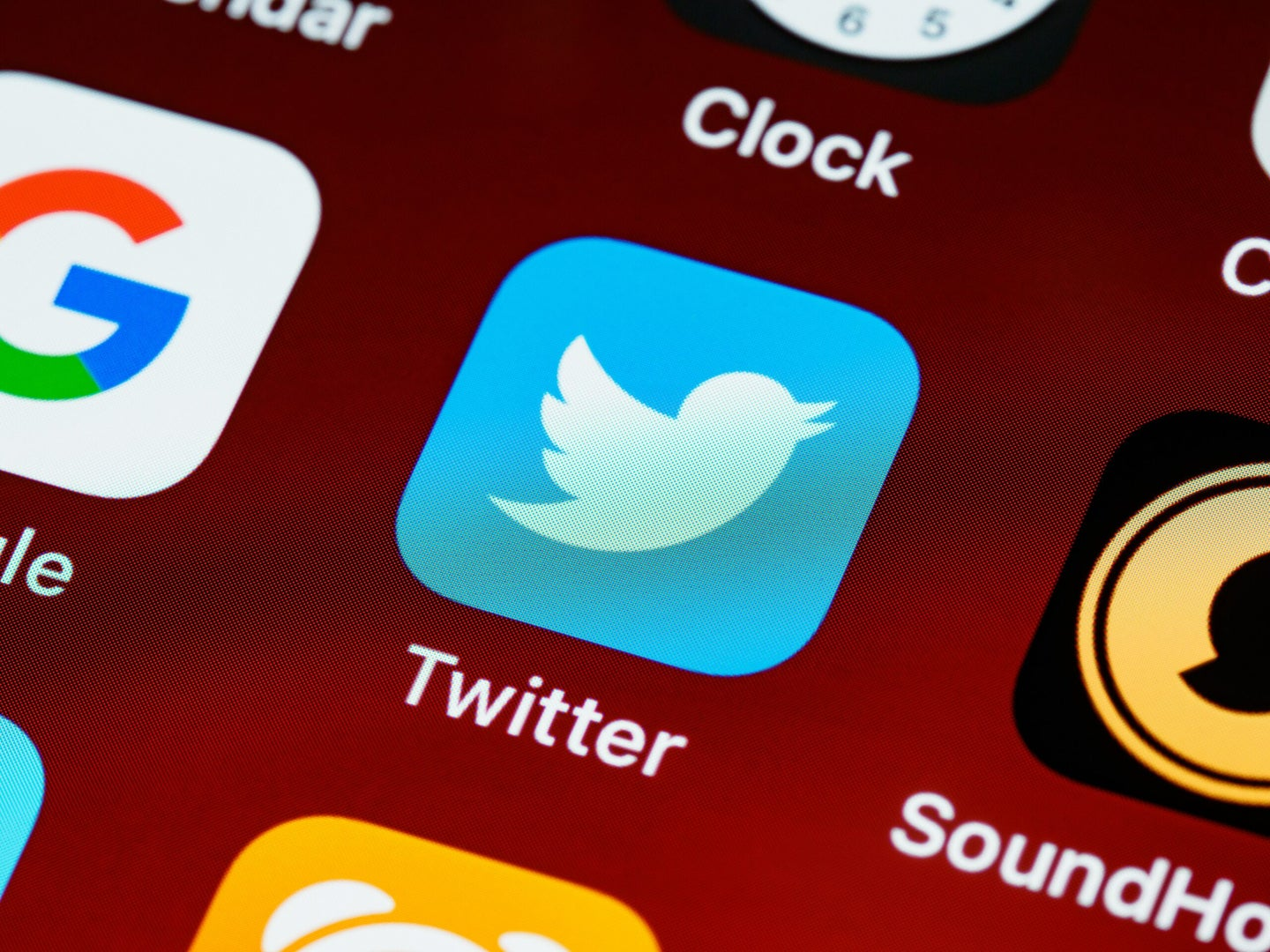 Twitter icon on a smartphone with other app icons.