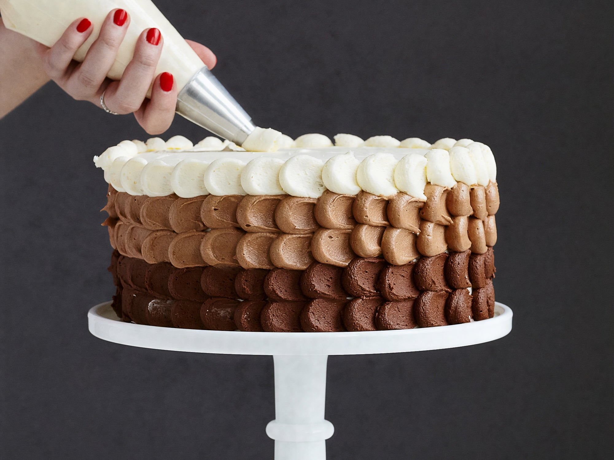 A person using a piping bag to pipe frosting onto a chocolate cake.