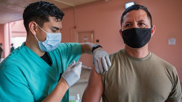 Hawaiian National Guard member gets a COVID-19 vaccine from a health care worker in scrubs