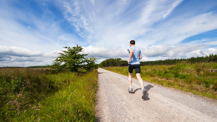 A guy running next to fields in a pair of the best running shoes for men