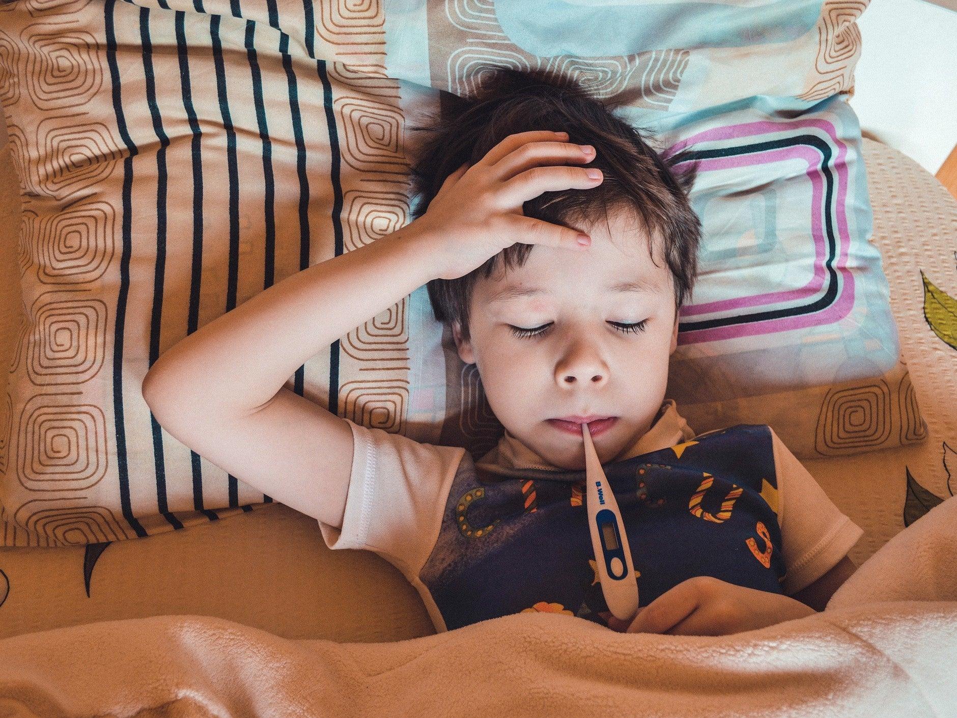 a kid sick in bed having his temperature taken