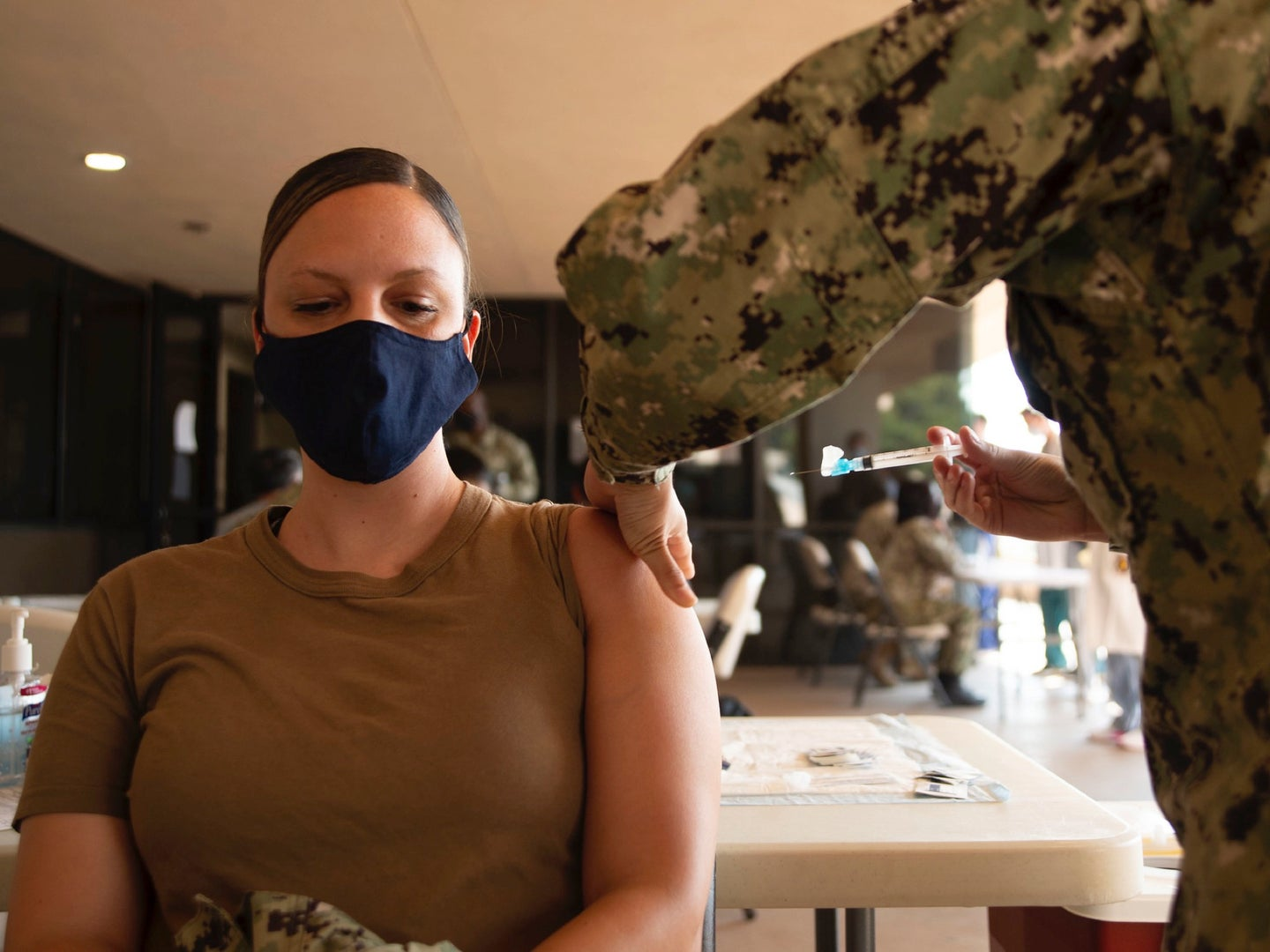 woman with a mask on gets a vaccine
