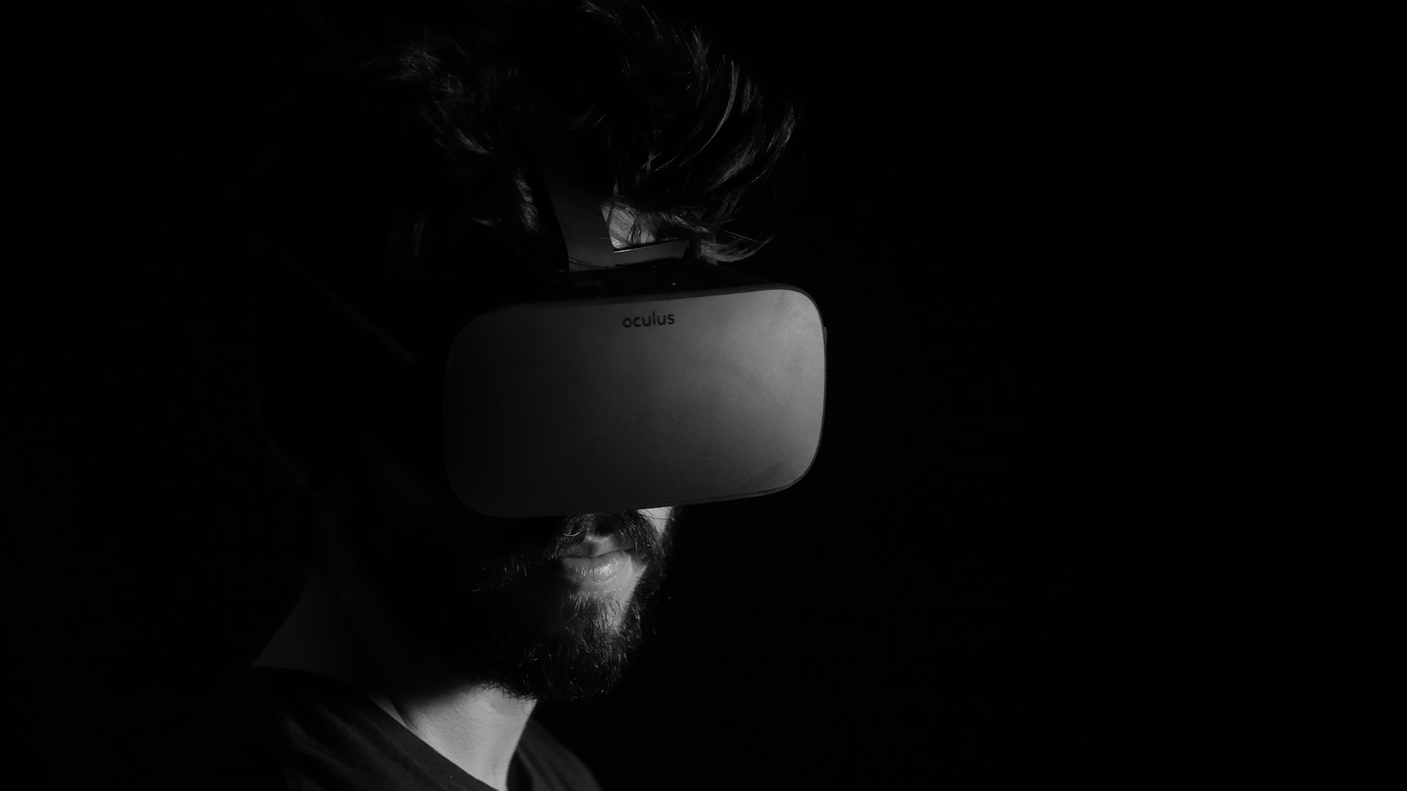 black and white photo of a man with oculus vr headset on