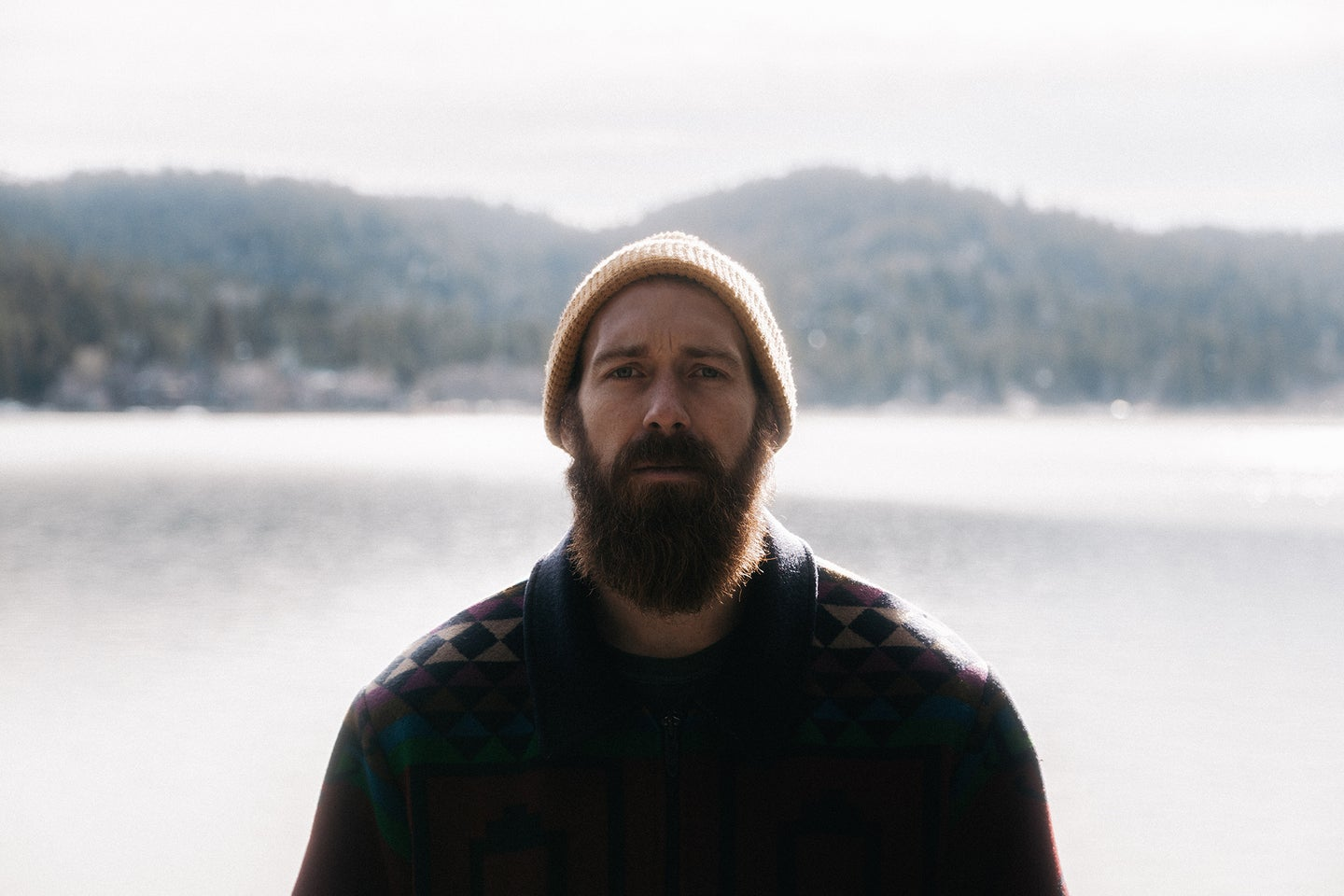 man standing in front of lake with a big beard and a beanie
