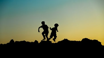 children silhouetted on hill