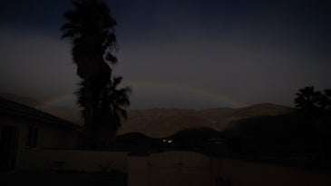 A lunar rainbow or moonbow stretching over the mountains at night in Anza-Borrego Desert State Park