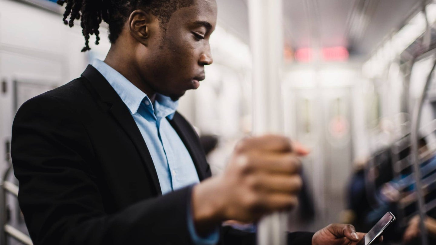 Person on a New York City subway train texting on their phone.