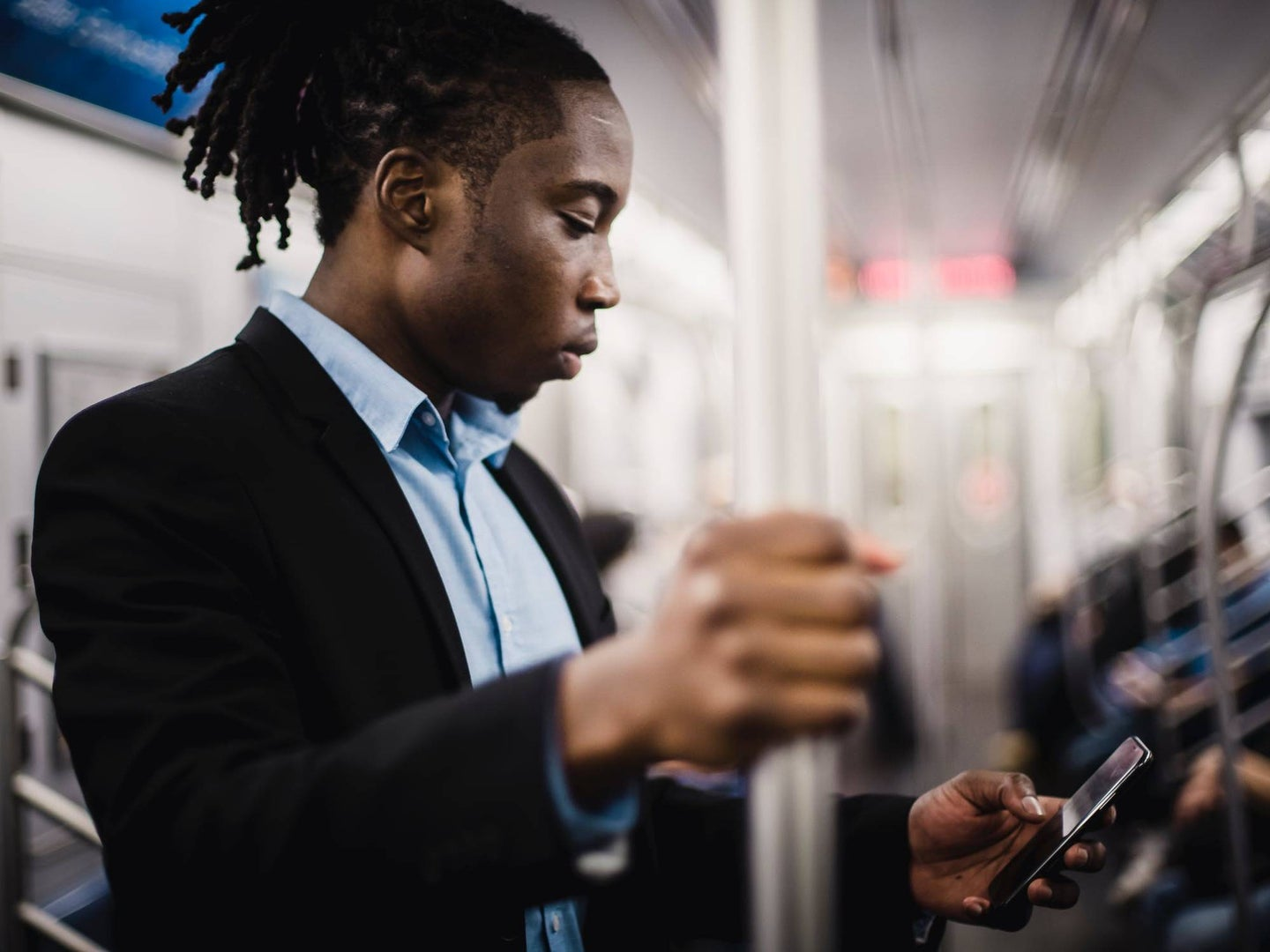 Person in New York train texting on their phone.