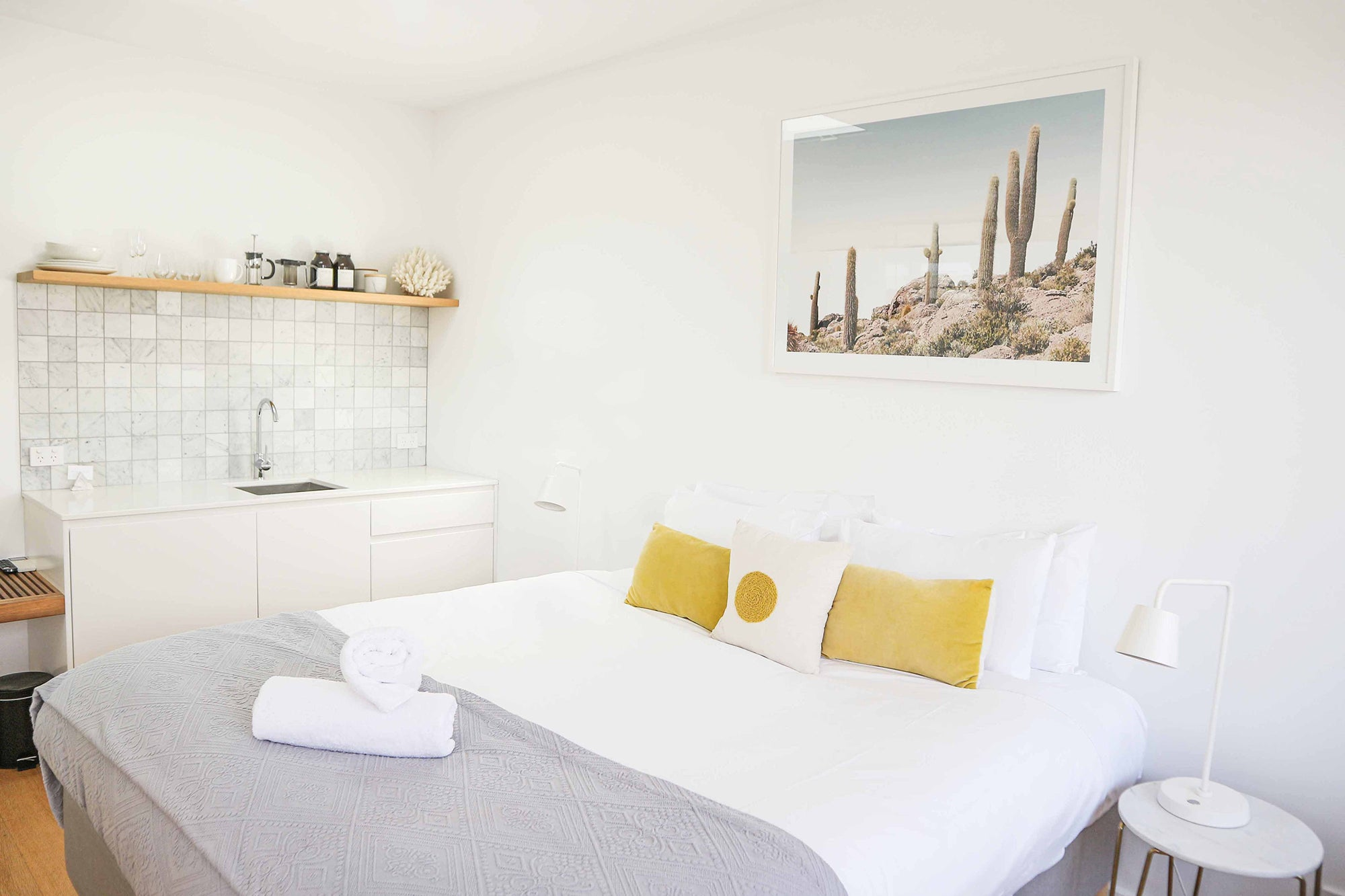 bedroom with a bed, sink, and yellow pillows