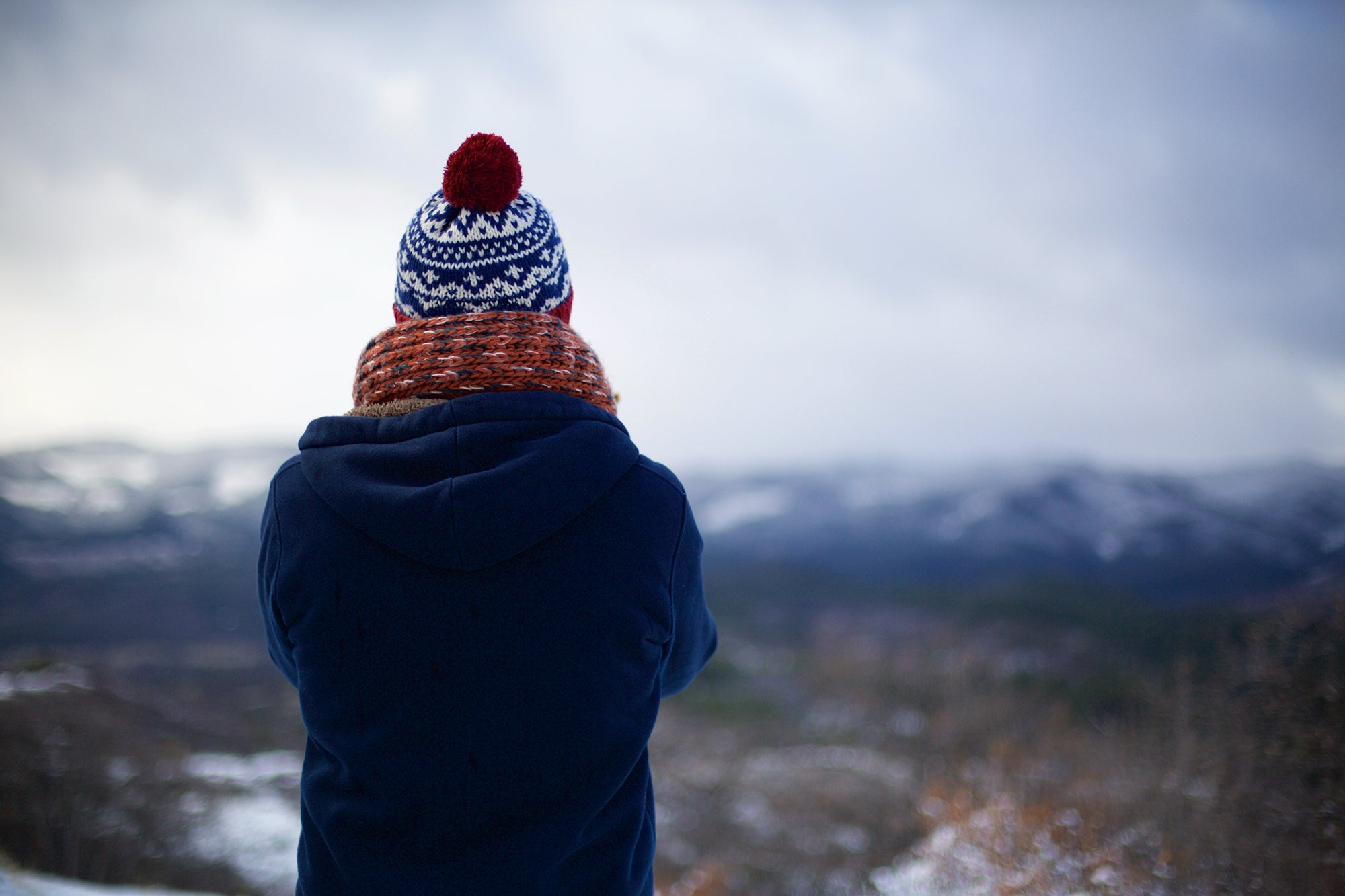 person with a winter hat and scarf looking out at a mountain