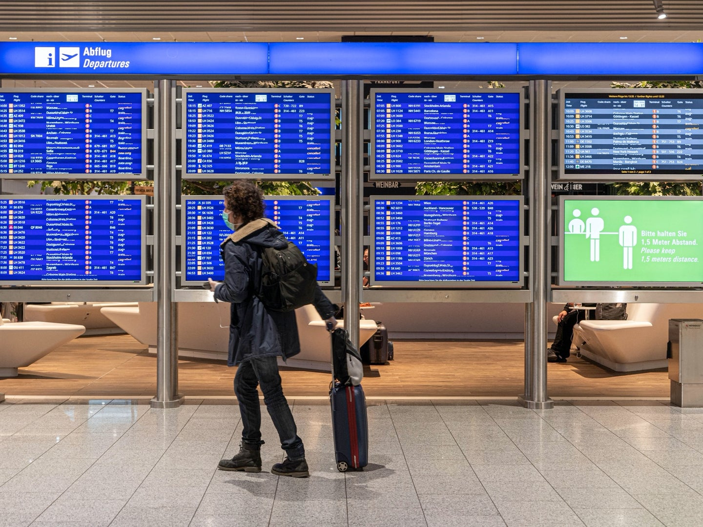 person wearing a mask and looking at the departures board at an airport