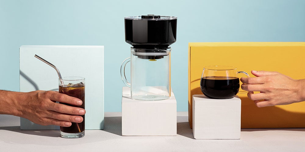 coffee maker and hands holding an iced coffee and hot coffee