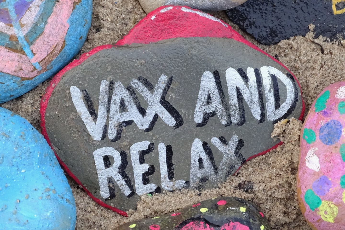 A beach rock painted with the phrase vax and relax for the COVID-19 pandemic