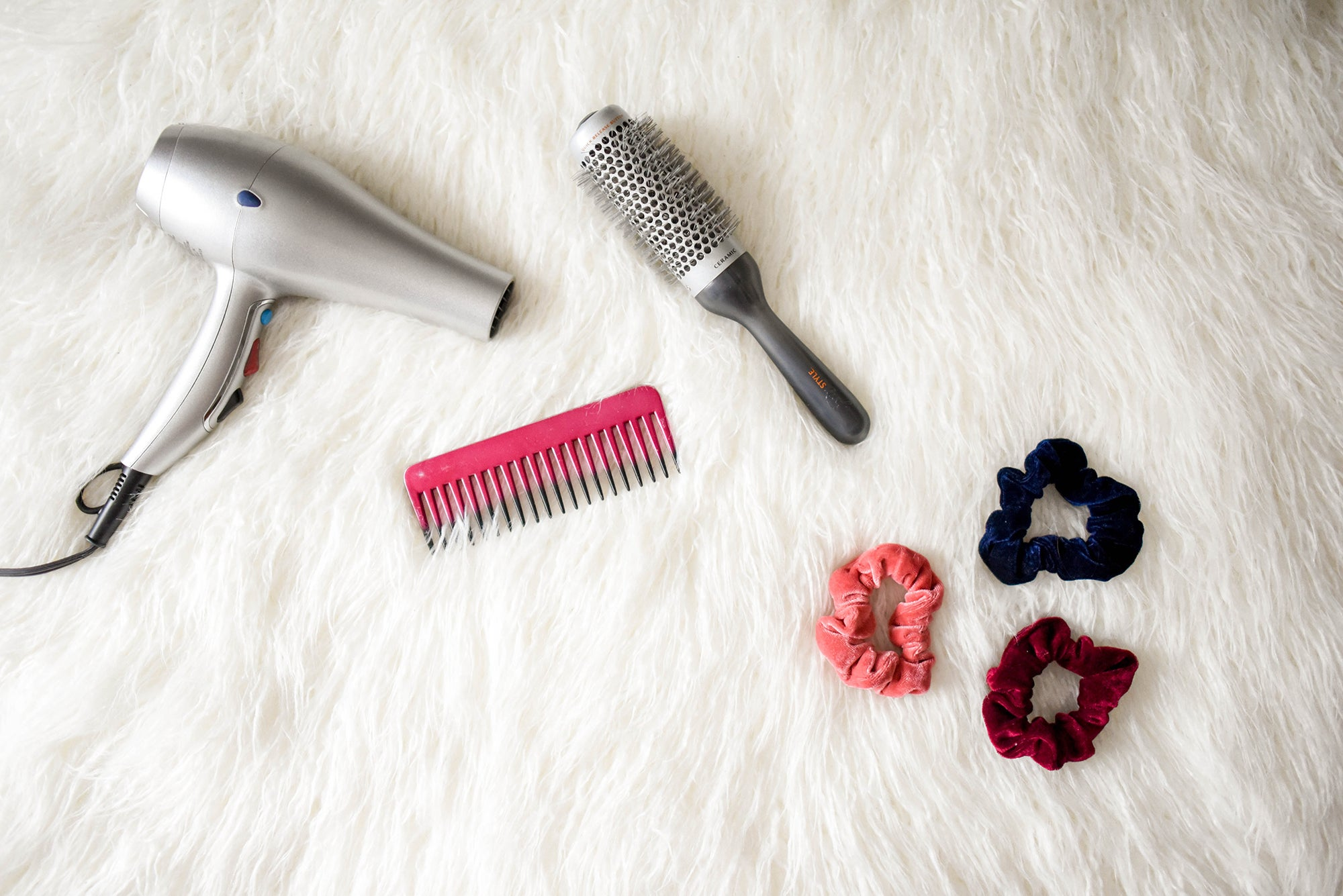 hair dryer, comb, brush, and scrunchies on a furry white rug