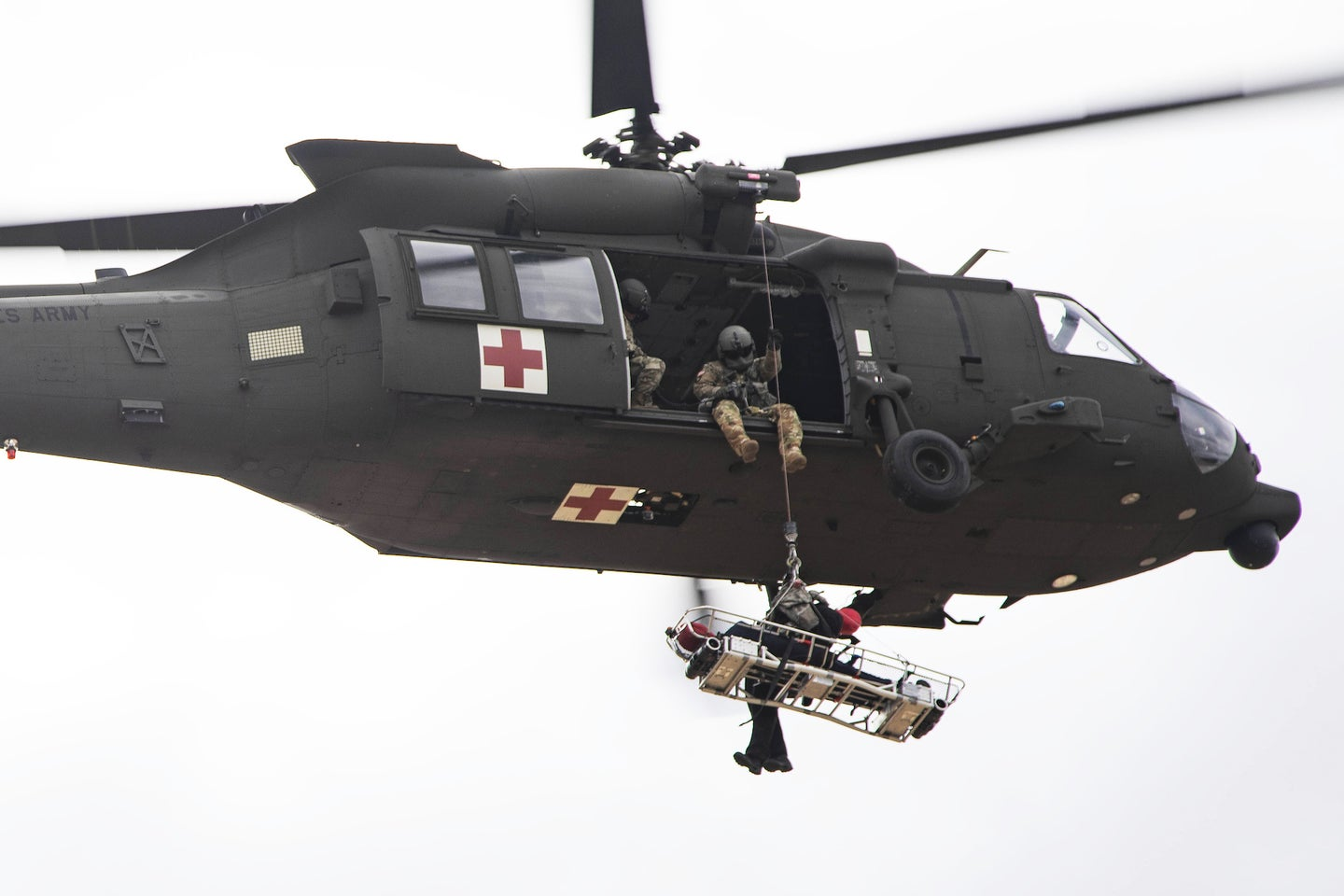 A Black Hawk helicopter with a rescue basket beneath it.
