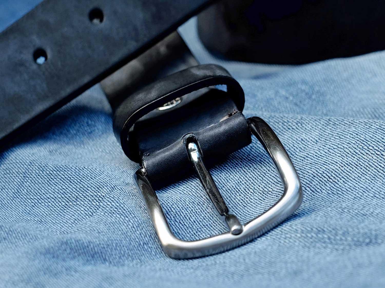 Black belt sitting on jeans.