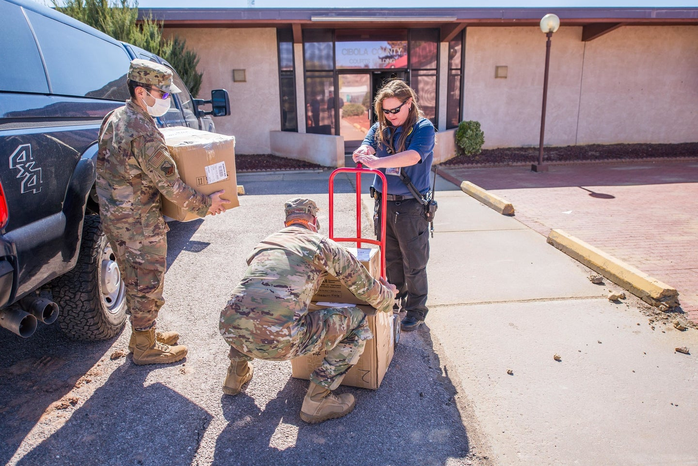 National Guard members dressed in camo dropping off COVID-19 PPE at a health clinic in New Mexico