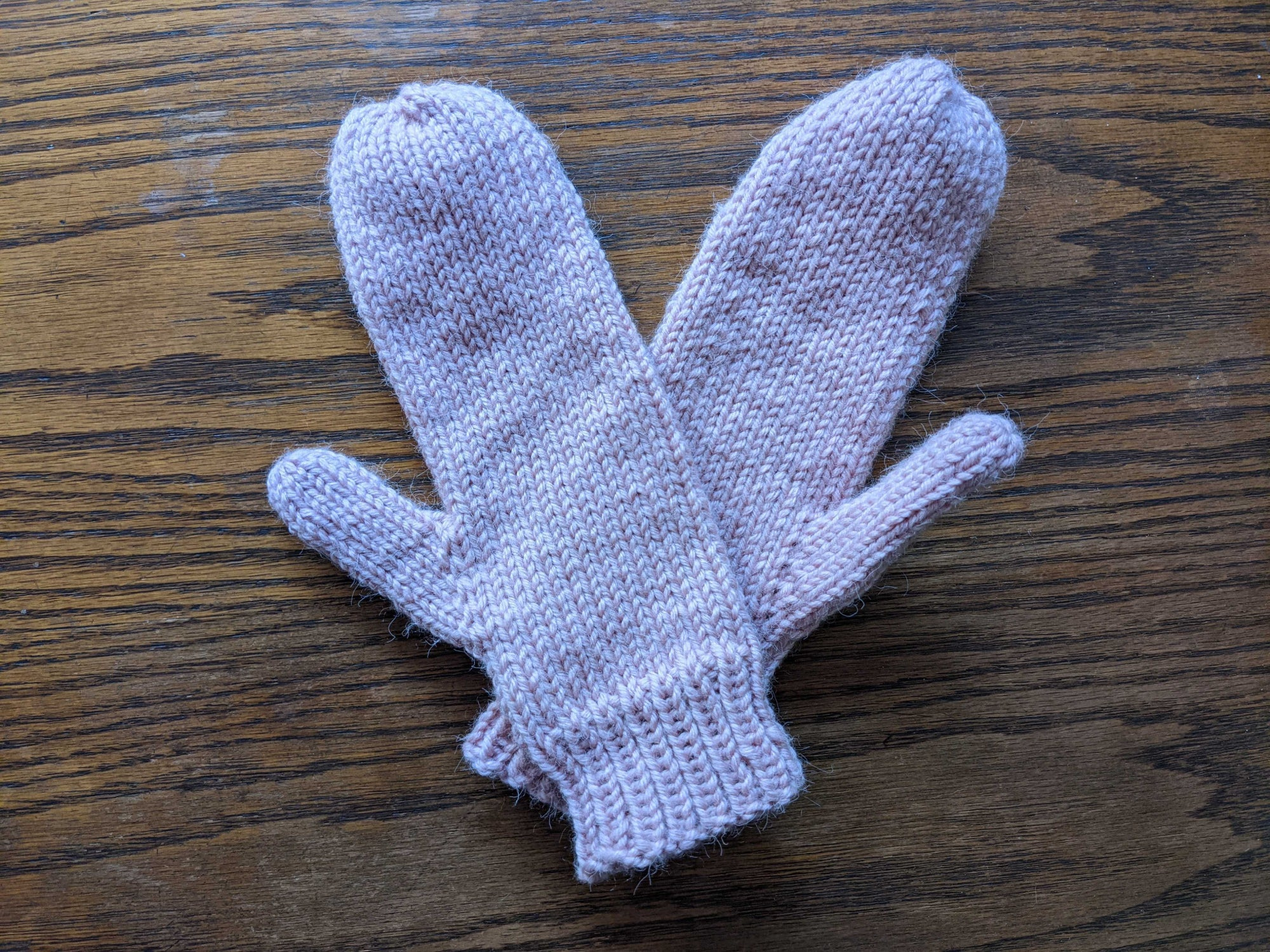 A pair of pink mittens on a wood surface.