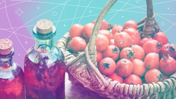 Basket of pomegranate fruits with glass bottles of tea on a light purple and seagreen background