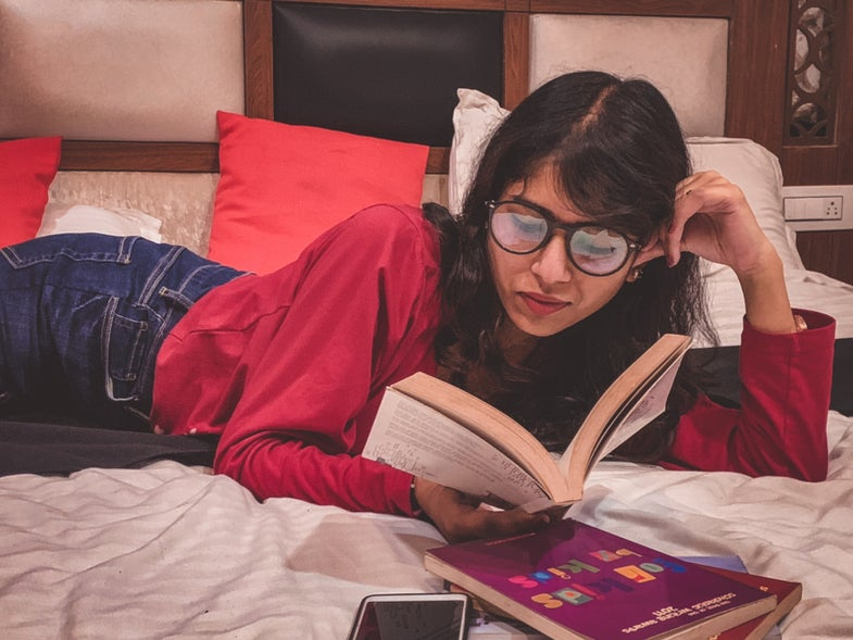 A person wearing glasses and laying on a bed while reading a book.