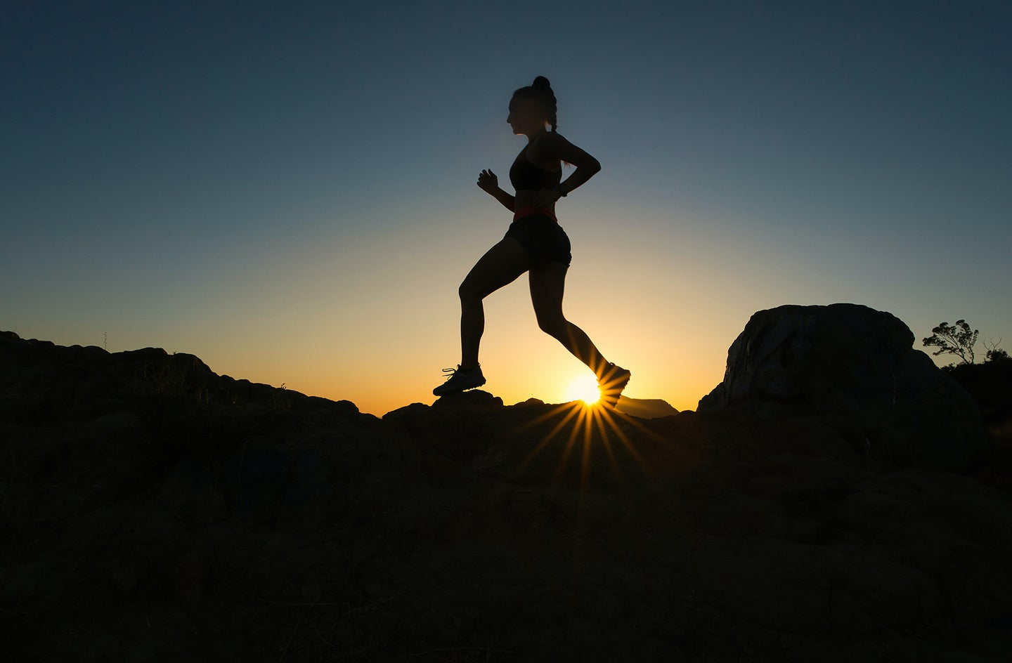 woman running on top of rocks with sun setting behind her