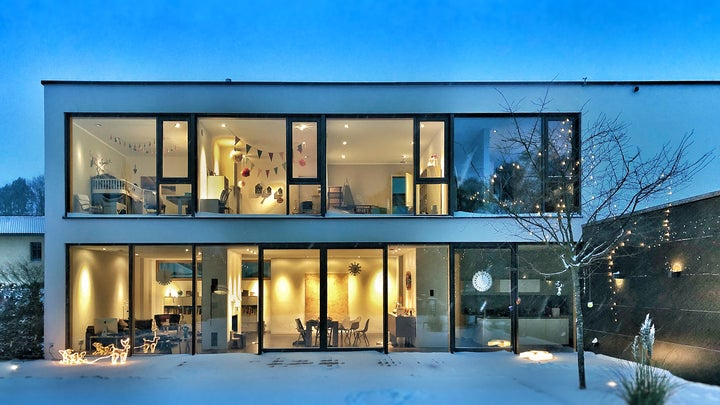 modern house with two floors, the best home security system cameras, and lights on inside