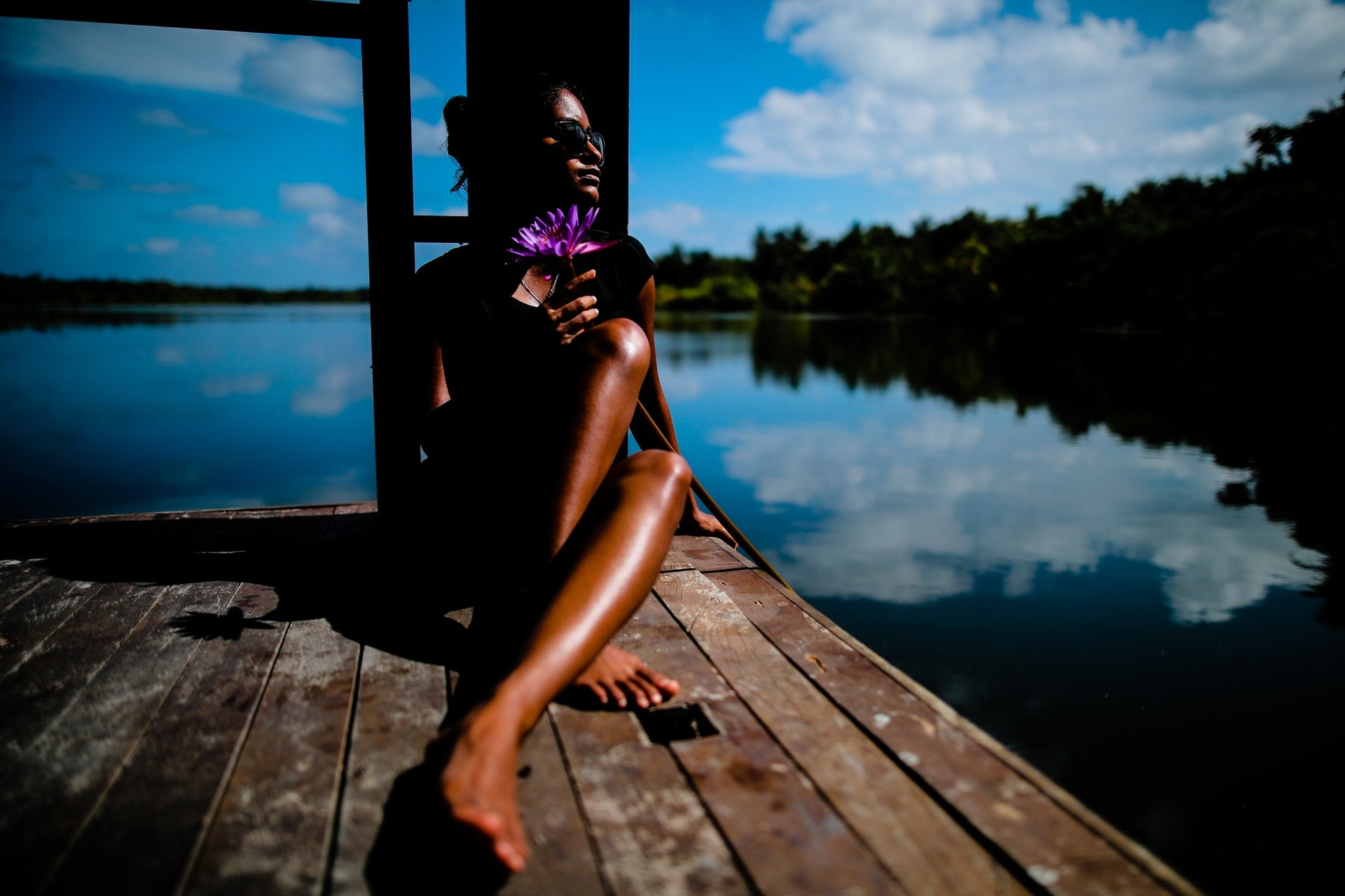 A person with dark brown skin tanning on a dock on a lake