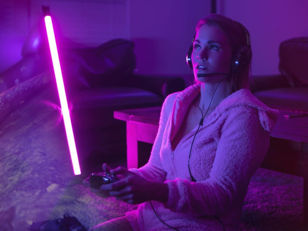 Person playing video games in the dark with a pink neon light